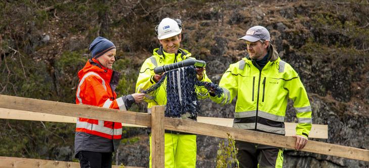 Tre personer i arbeidstøy ser på refugiumfelle